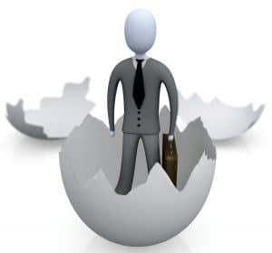 Royalty-free 3d generated business clipart picture graphic of a businessman carrying a briefcase and coming out of an eggshell.